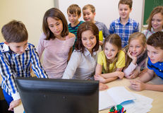 Grupa dzieciaki z nauczycielem i komputerem przy szkołą Zdjęcia Stock