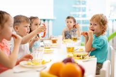 Grupa dziecinów ucznie je zdrową karmową przerwę na lunch wpólnie obraz royalty free