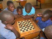 Grupa dziecko w wieku szkolnym bawić się szachy i ogląda Obrazy Stock