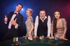 Grupa eleganccy bogaci przyjaciele bawić się grzebaka przy kasynem obraz stock