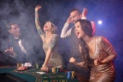 Grupa eleganccy bogaci przyjaciele bawić się grzebaka przy kasynem obrazy stock