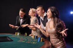 Grupa eleganccy bogaci przyjaciele bawić się grzebaka przy kasynem zdjęcie royalty free
