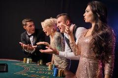 Grupa eleganccy bogaci przyjaciele bawić się grzebaka przy kasynem zdjęcia stock