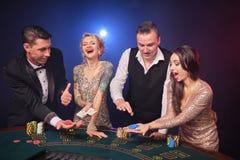 Grupa eleganccy bogaci przyjaciele bawić się grzebaka przy kasynem zdjęcia royalty free