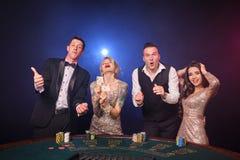 Grupa eleganccy bogaci przyjaciele bawić się grzebaka przy kasynem obrazy royalty free