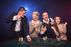 Grupa eleganccy bogaci przyjaciele bawić się grzebaka przy kasynem fotografia stock