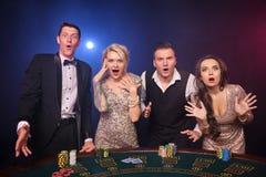 Grupa eleganccy bogaci przyjaciele bawić się grzebaka przy kasynem zdjęcie stock