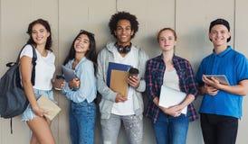 Grupa etniczni nastoletni ucznie z falc?wkami i szkolnymi torbami obrazy stock
