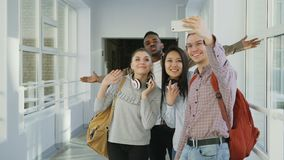 Grupa etniczni ucznie bierze selfie na smartphone kamerze podczas gdy stojący w korytarzu uniwersytet Modnisia facet zdjęcie wideo
