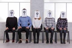 Grupa faceci i dziewczyny, siedzi na krzesłach, ręki na ich kolanach na ich twarzach i jest znakiem zapytania zdjęcia royalty free