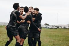 Grupa gracz futbolu z podnieceniem na zdobywać punkty cel Futboliści nadchodzący w skupisko odświętności zwycięstwie na polu wpól fotografia royalty free