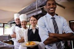 Grupa hotel obsdza personelem pozycję z armas krzyżującymi w kuchni zdjęcia royalty free