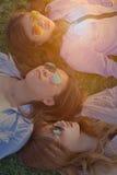 Grupa kobiety z okularami przeciwsłonecznymi dalej, kłaść puszek na zielonej trawie obrazy stock