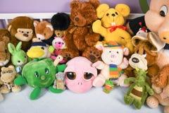 Grupa kolorowe puszyste faszerowa? zwierz?ce zabawki zamyka w g?r? bia?y drewniany dziecka ?ci?ga wewn?trz zdjęcie stock
