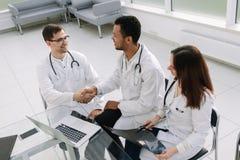 Grupa lekarki dyskutuje pacjent medyczną historię przy pracującym spotkaniem obraz royalty free