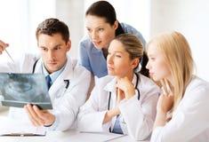 Grupa lekarki patrzeje promieniowanie rentgenowskie obraz stock