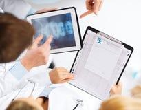 Grupa lekarki patrzeje promieniowanie rentgenowskie na pastylka komputerze osobistym Zdjęcie Stock