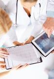 Grupa lekarki patrzeje promieniowanie rentgenowskie na pastylka komputerze osobistym Obraz Stock
