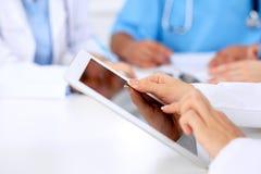 Grupa lekarki przy medycznym spotkaniem Zamyka up lekarz używa pastylka komputer Zdjęcie Stock