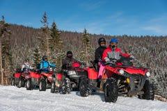 Grupa ludzi na kołodziejach ATV jechać na rowerze na śniegu w zimie obrazy stock