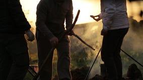 Grupa ludzi obok ogniska przy zmierzchem, sylwetka zbiory