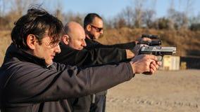 Grupa ludzi praktyki pistoletu krótkopęd na celu na plenerowym mknącym pasmie obraz stock