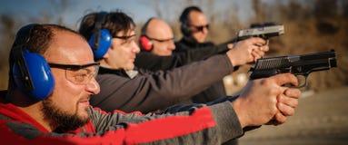 Grupa ludzi praktyki pistoletu krótkopęd na celu na plenerowym mknącym pasmie fotografia stock