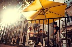 Grupa ludzi spotkanie pije i śmia się przy plenerową restauracją z, słońce napojami i parasolem zdjęcia royalty free