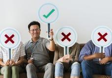 Grupa ludzi trzyma prawdziwe & fałszywe ikony Obraz Stock