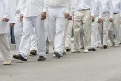 grupa ludzi w biel ubraniach mężczyzna w białych jeleniach chodzą w dół ulicę fotografia royalty free