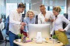 Grupa ludzi w biurowym patrzeje komputerze zdjęcia royalty free
