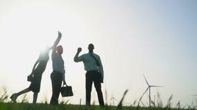 Grupa ludzi w garniturach daje wysokości pięć przy wiatrowych generatorów tłem, zwolnione tempo zbiory wideo