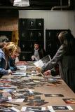Grupa ludzi w księgarni 3 sztuki ławki kosza podłoga obramia drewniane galerii ściany wewnętrzne purpurowe proste zdjęcia stock