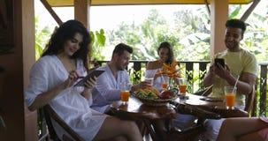 Grupa Ludzi Z komórka telefonów Mądrze przesyłanie wiadomości Sititng przy stołem Na lato tarasie, mieszanka Biegowych mężczyzna  zbiory