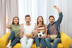 Grupa ludzi z przekąskami i balowym dopatrywanie meczem piłkarskim na TV zdjęcia stock