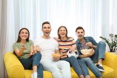Grupa ludzi z przekąskami i balowym dopatrywanie meczem piłkarskim na TV obraz royalty free