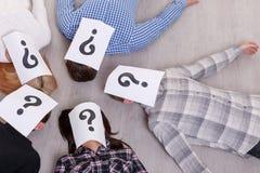 Grupa ludzi z zamkniętymi twarzami z znakiem zapytania na podłoga na lewicie Obrazy Stock
