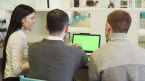 Grupa ludzie biznesu dyskutuje coś na zielenieje parawanowego laptop zdjęcie wideo
