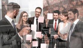 Grupa ludzie biznesu patrzeje notatki na szkle zdjęcie royalty free