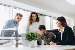 Grupa młodzi partnery biznesowi pracuje w nowożytnym biurze Coworkers ma kłopot podczas gdy pracujący na laptopie obraz stock