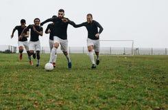 Grupa mężczyźni bawić się piłkę nożną na polu obraz royalty free