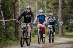 Grupa męscy cykliści jedzie przez lasu Fotografia Stock