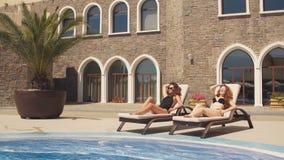 Grupa młode kobiety ma słońca skąpanie, kłama na deckchair blisko hotelowego basenu zbiory wideo