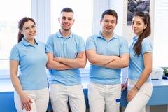 Grupa młody i szczęśliwy stomatologiczny lekarka stojak blisko each inny przy stomatologiczną kliniką Pracy zespo?owej i biznesu  zdjęcie stock