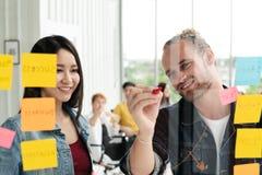 Grupa młody pomyślny kreatywnie wieloetniczny drużynowy ono uśmiecha się wpólnie i brainstorm obraz stock