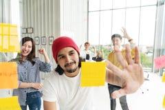 Grupa młody pomyślny kreatywnie wieloetniczny drużynowy ono uśmiecha się wpólnie i brainstorm w nowożytnym biurze Mężczyzna i kob obraz stock