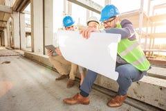Grupa młodzi architekci patrzeje podłogowych plany podczas inspekcji budowa zdjęcie stock