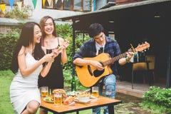 Grupa młodzi azjatykci ludzie szczęśliwi podczas gdy cieszący się ogrodowego przyjęcia zdjęcia royalty free