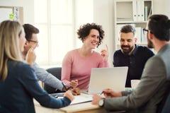 Grupa młodzi biznesmeni siedzi wokoło stołu w nowożytnym biurze, mieć spotkania fotografia stock