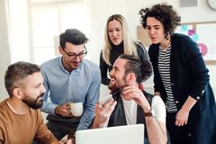 Grupa młodzi biznesmeni z laptopem pracuje wpólnie w nowożytnym biurze obrazy stock